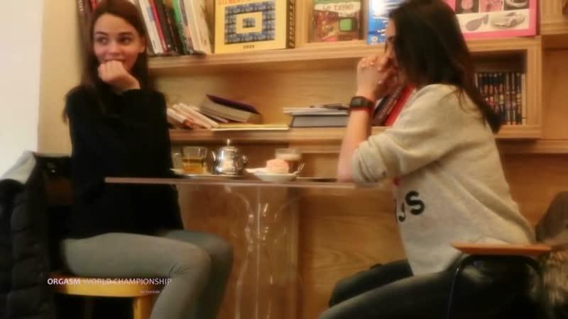 две девочки две игрушки с дистанционным управлением и стол в переполненом кафе. orgasm world championship