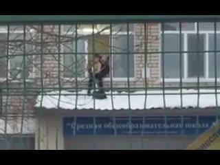 Школьник из Уссурийска чистит снег на козырьке