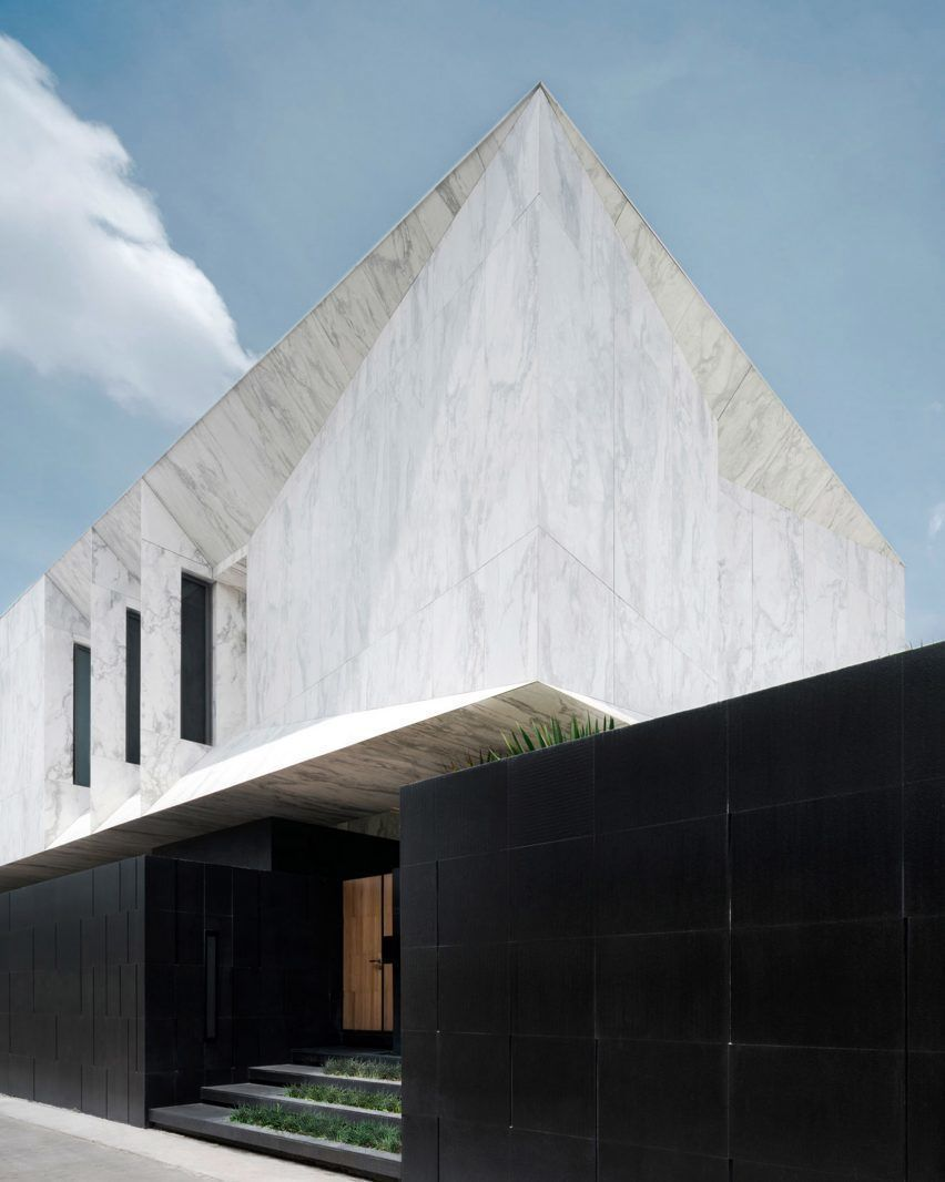 Wedge-shaped chunks are carved out of the marble-clad volume of this house inBangkok, Thailand, which was designed by local studio Openbox Architects.