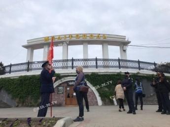 Дюжина полицейских в Мелитополе пытается убедить пенсионера с красным флагом уйти с Аллеи Славы (фото, видео)
